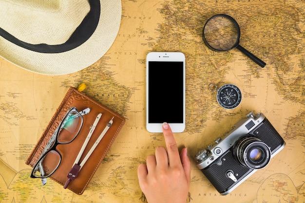 Menselijke hand op mobiele telefoon met reizende apparatuur rond op de kaart