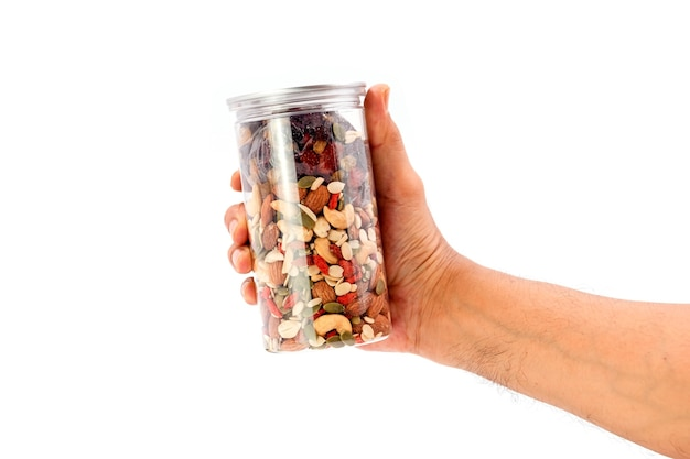 Menselijke hand volle granen en gedroogde vruchten plastic fles geïsoleerd op een witte achtergrond.