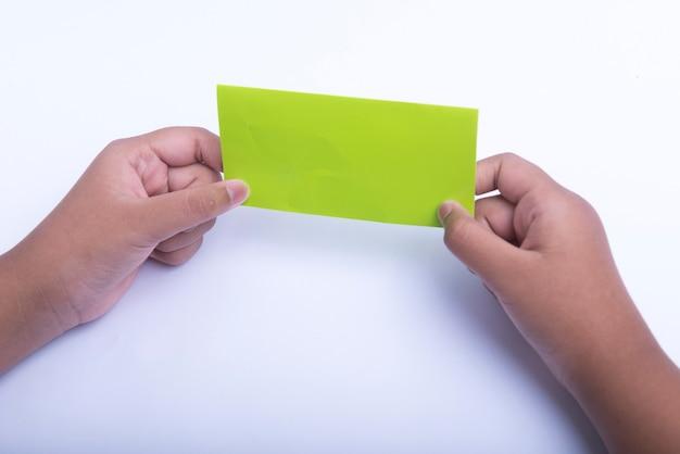 Menselijke hand vouwen van een gekleurd papier geïsoleerd op witte achtergrond