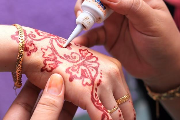 Menselijke hand wordt versierd met henna-tatoeage