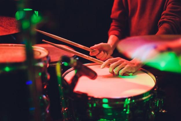Menselijke handen die de trommel met drumstick spelen.