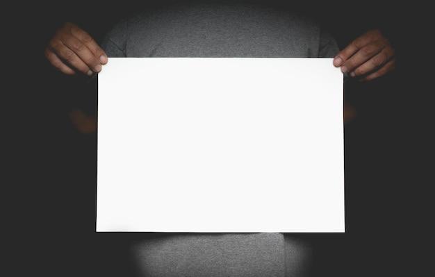 Menselijke handen die lege reclamekaart houden. mens die aanplakbiljet klaar toont en toont