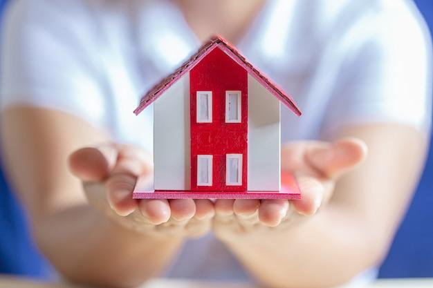 Menselijke handen die model van droomhuis houden