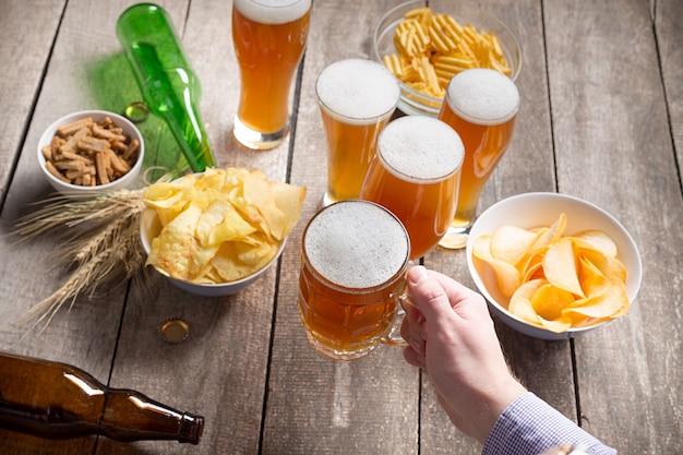 Menselijke handen en glazen bier