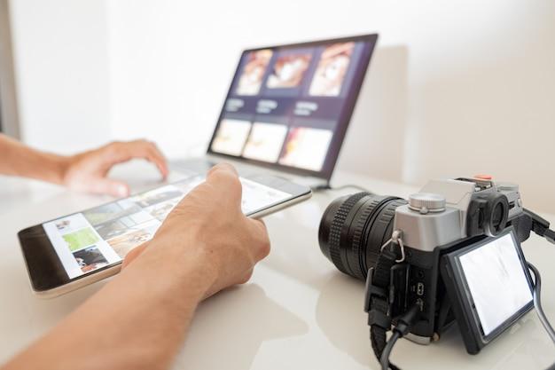 Menselijke handen houden een tablet vast om foto's te ordenen of te importeren van camera naar laptop