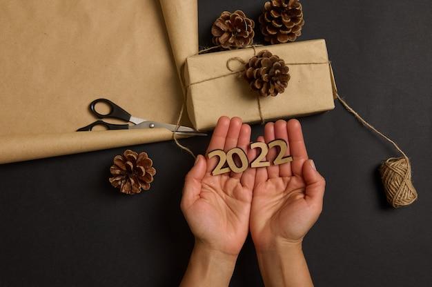 Menselijke handen houden houten cijfers 2022 vast tegen de achtergrond van een kerstcadeaudoos verpakt in ambachtelijk papier versierd met dennenappels liggend op een zwart oppervlak met touw en schaar. kerst ontwerp
