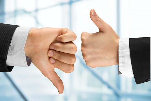 Menselijke handen met eens-teken versus oneens op de achtergrond