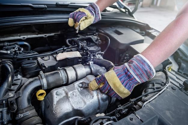 Menselijke handen met moersleutels in beschermende handschoenen op automotor