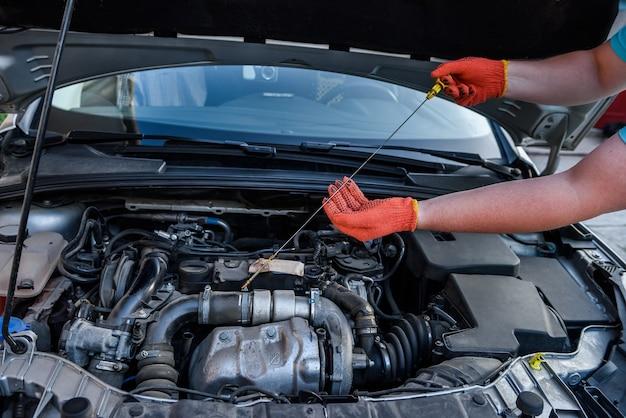 Menselijke handen met oliepeilmeter tegen automotor