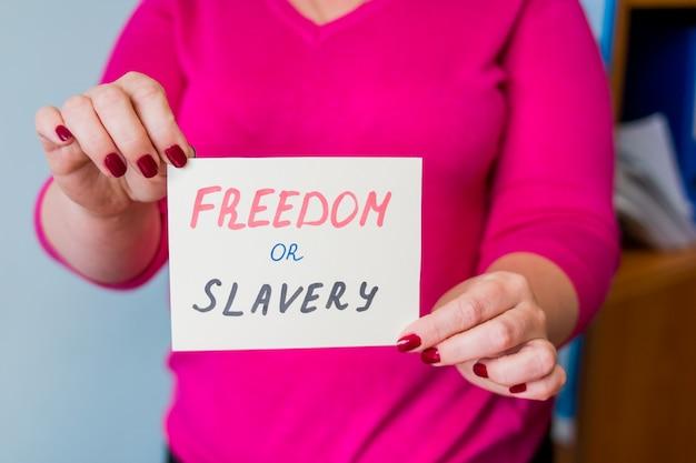 Menselijke handen met papier met tekstvrijheid of slavernij, beslissingsgids. vrijheidsconcept. nationale vrijheid dag