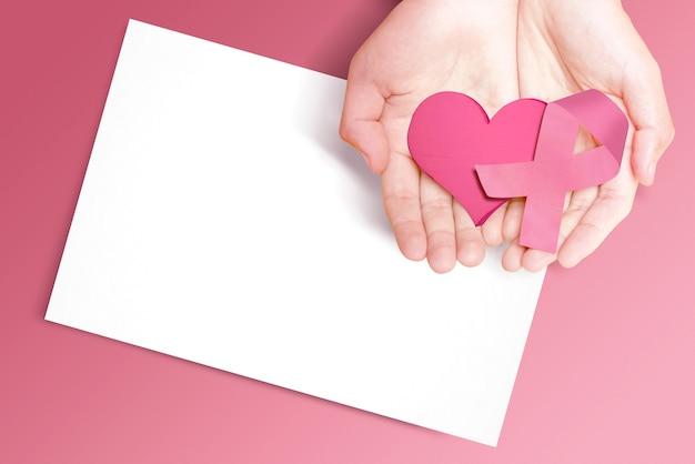 Menselijke handen met roze voorlichtingslint, hart en leeg papier. voorlichting over borstkanker. leeg papier voor kopie ruimte