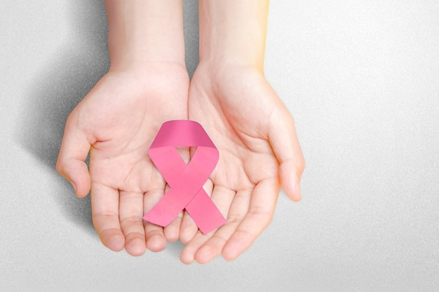 Menselijke handen met roze voorlichtingslint. voorlichting over borstkanker