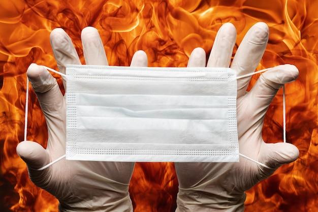 Menselijke handen met veel ademhalingsmaskers in witte medische handschoenen op achtergrondvlammen van sterk rood vuur. concept quarantaine, grippe, pandemische uitbraak, hygiëne.