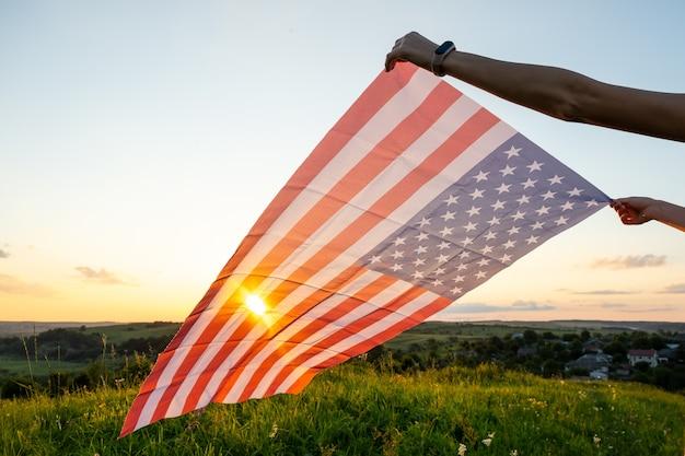 Menselijke handen met wuivende amerikaanse nationale vlag in veld bij zonsondergang.