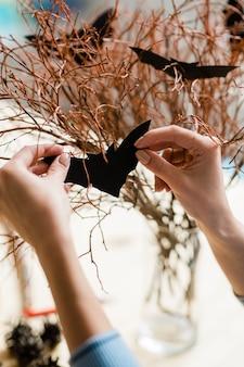Menselijke handen met zwarte papieren vleermuis die droge takken voor halloween verfraait tijdens de voorbereiding op vakantie