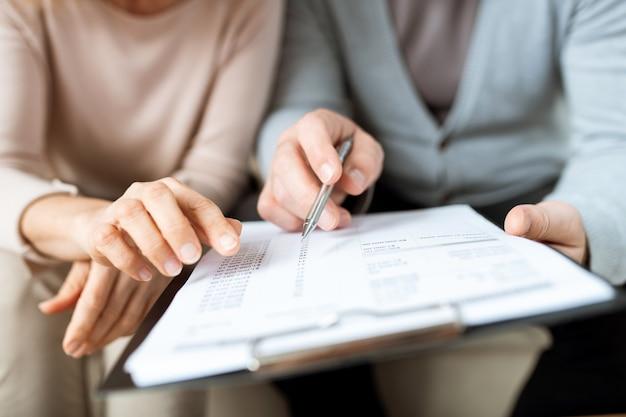 Menselijke handen wijzen op een van de punten van het contract of een ander document terwijl ze ze lezen voordat ze ondertekenen