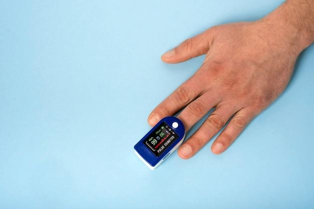 Menselijke handpulsoximeter die wordt gebruikt om de polsslag en zuurstofniveaus te meten met medische blauwe achtergrond met kopie ruimte.