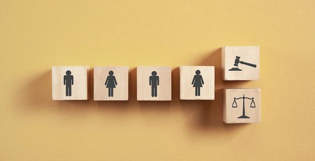 Menselijke pictogrammen, rechterhamer en schalen op houten kubussen.