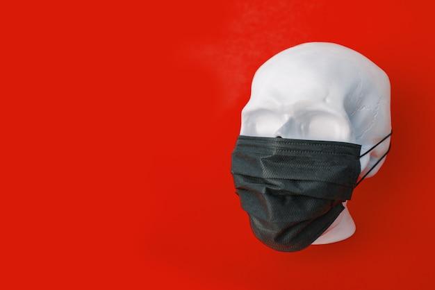 Menselijke schedel die een beschermend mondmasker draagt. geïsoleerd op een rode achtergrond