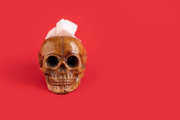 Menselijke schedel gevuld met geraffineerde witte suikerklontjes op een rode achtergrond. selectieve aandacht. ruimte kopiëren.