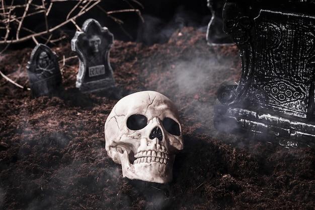 Menselijke schedel in rook bij halloween-begraafplaats Premium Foto