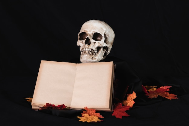 Menselijke schedel met boek op zwarte achtergrond