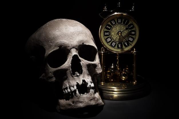 Menselijke schedel met uitstekende klok dichte omhooggaand op zwarte