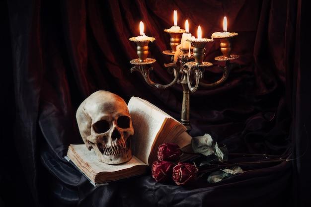 Menselijke schedel op boek met antieke kandelaar. stilleven