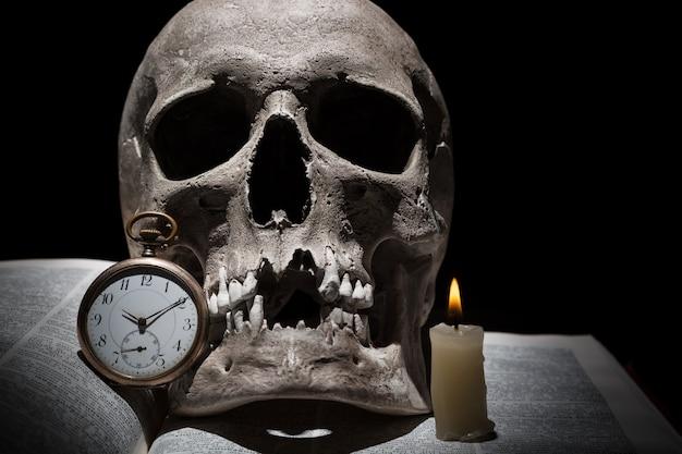Menselijke schedel op oud open boek met dicht omhoog het branden van kaars en uitstekende klok op zwarte achtergrond onder lichtstraal
