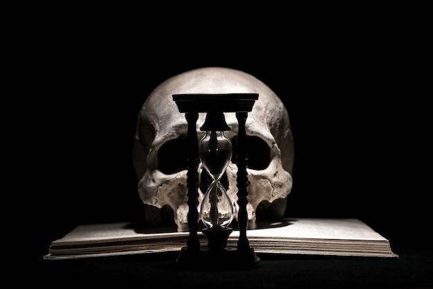 Menselijke schedel op oud open boek met vintage zandloper op zwart.