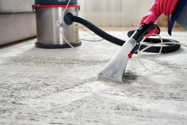Menselijke tapijt in de woonkamer met behulp van stofzuiger thuis