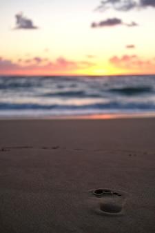 Menselijke voetafdruk op het zandstrand dat glanst onder de zonsondergang