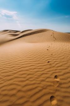 Menselijke voetafdrukken in het zand in de woestijn
