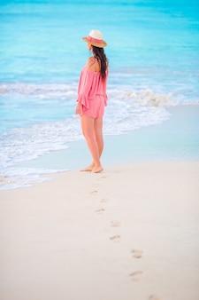Menselijke voetafdrukken op het witte zandstrand met mooie jonge vrouwenachtergrond