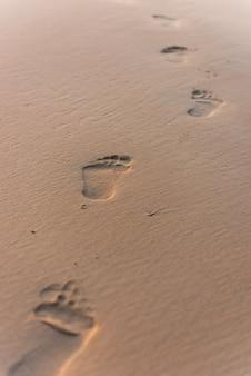 Menselijke voetafdrukken op strandzand.