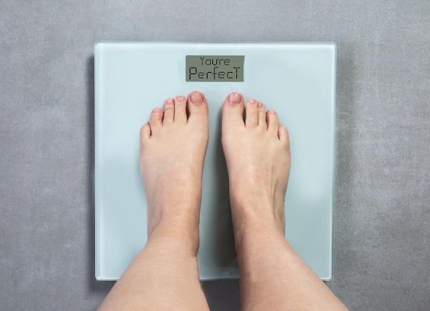 Menselijke voeten op digitale weegschaal met de woorden: je bent perfect, zelfvertrouwen en dieetconcept