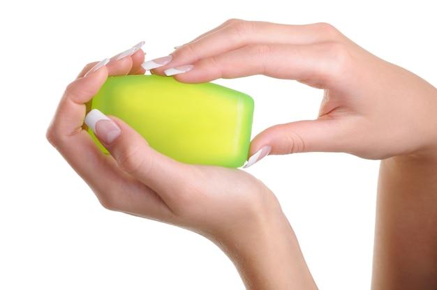 Menselijke vrouwelijke handen met de groene zeep