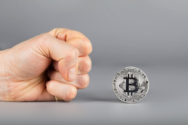 Menselijke vuist en bitcoin. detailopname