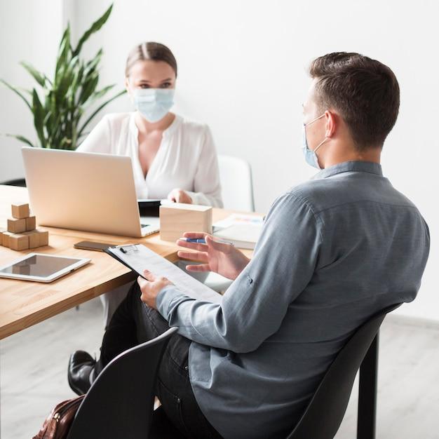 Mensen aan het werk op kantoor tijdens pandemie die medische maskers dragen