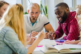 Mensen aan tafel die ideeën bestuderen en delen