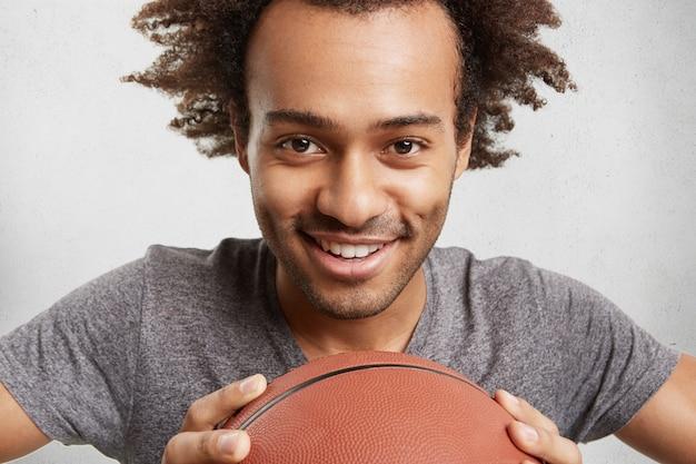 Mensen, actieve levensstijl en sportconcept. vrolijke mannelijke tiener met afro-kapsel