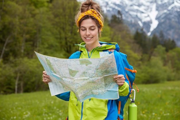 Mensen, avontuur en trekkingconcept. gelukkig vrouwelijke toerist houdt papieren kaart, wandelingen op vallei in de buurt van bergen