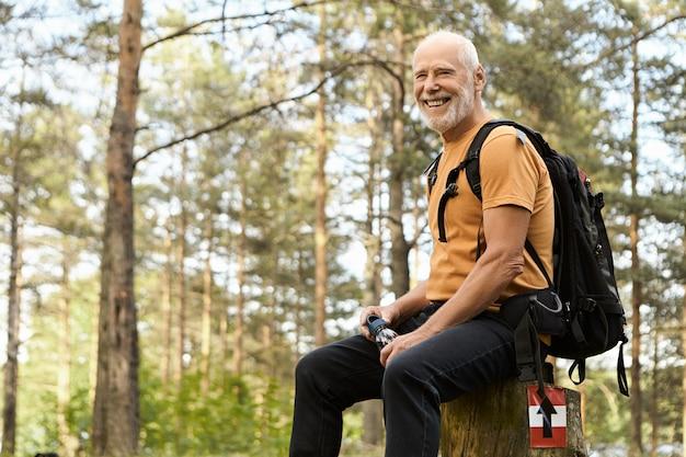 Mensen, avontuur, reizen en actief gezond levensstijlconcept. vrolijke energieke oudere man wandelen met rugzak in het bos, rust op boomstronk, drinkwater met pijnbomen erin