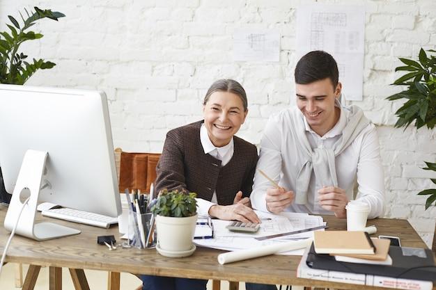 Mensen, baan, teamwerk en samenwerkingsconcept. gelukkig middelbare leeftijd vrouwelijke hoofdingenieur plezier in kantoor terwijl iets uit te leggen aan haar jonge mannelijke assistent, zittend aan een bureau met pc en papieren