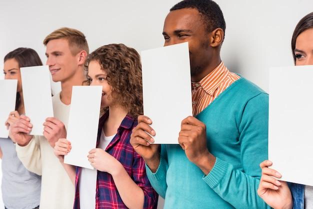 Mensen bedekken hun gezicht met wit papier.