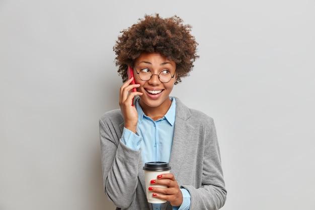 Mensen bedrijfs- en communicatieconcept. blij dat de donkere afro-amerikaanse vrouw een telefoongesprek heeft