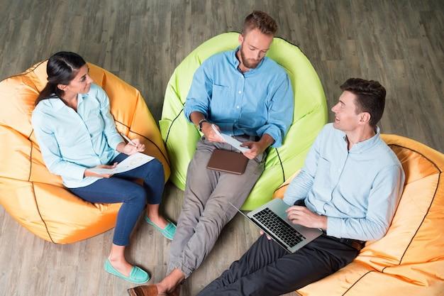 Mensen bespreken project over beanbag stoelen