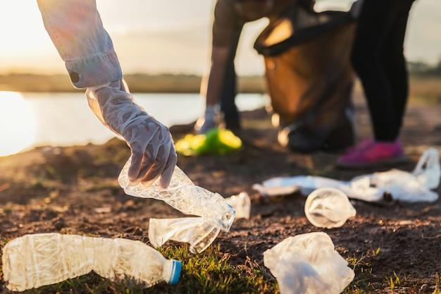 Mensen bieden vrijwilliger afval plastic fles aan in zwarte tas bij park rivier in zonsondergang