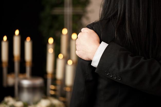 Mensen bij begrafenis troosten elkaar