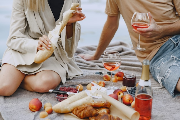 Mensen bij de rivier. heerlijke gezonde zomerpicknick op het gras. vruchten op een blancet.